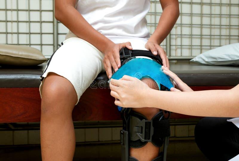 Terapeuta físico que aplica la compresa fría en rodilla paciente al rojo imagen de archivo libre de regalías