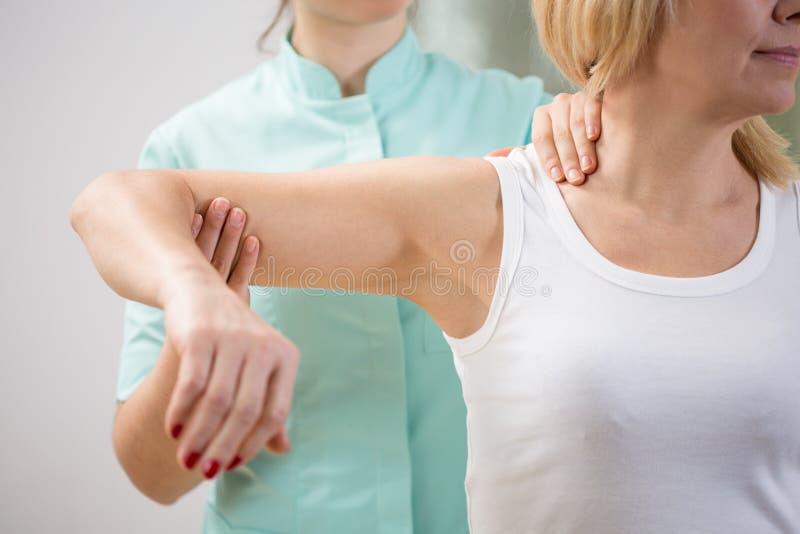 Terapeuta físico que diagnostica al paciente fotografía de archivo