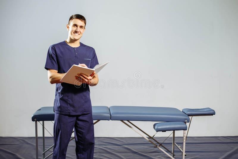 Terapeuta feliz novo no uniforme, o compartimento da massagem para o registro nas mãos perto do sofá da massagem fotos de stock royalty free