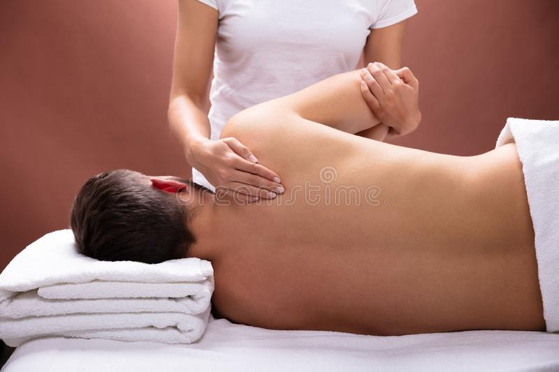 Terapeuta Giving Shoulder Massage a equipar fotografia de stock royalty free