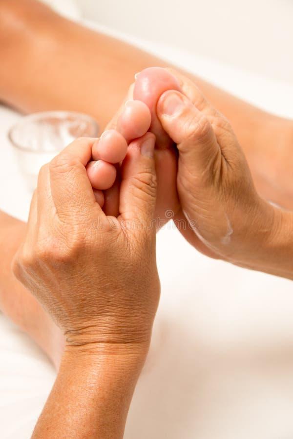 Terapeuta Massaging Giving da massagem uma massagem do pé fotografia de stock royalty free