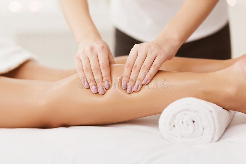 Terapeuta Massaging Woman Calves da massagem no centro dos termas foto de stock