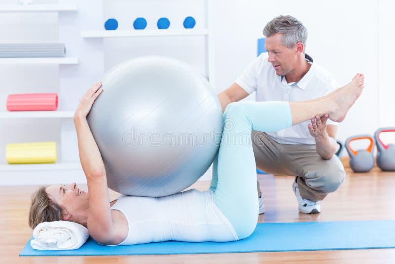Terapeuta pomaga jego pacjenta z ćwiczenie piłką obraz royalty free