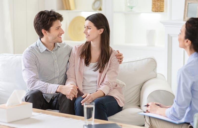 Terapeuta profissional e pares felizes no escritório imagens de stock