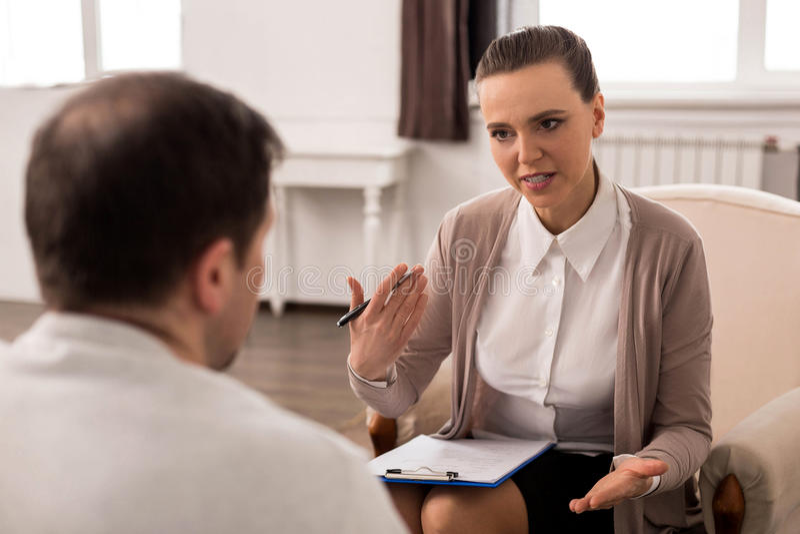 Terapeuta profissional positivo que dá o conselho foto de stock