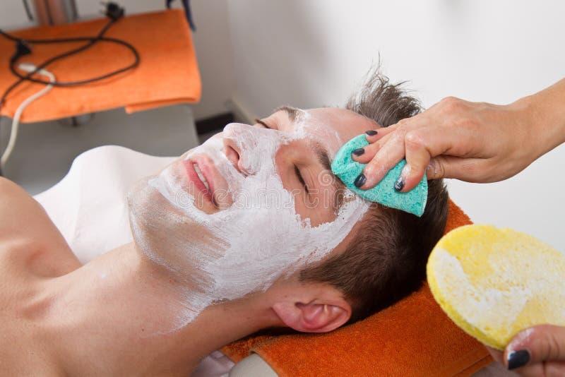 Terapeuta que aplica uma máscara protetora a um homem novo bonito em uns termas foto de stock