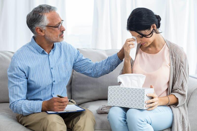 Terapeuta que consola uma mulher imagens de stock