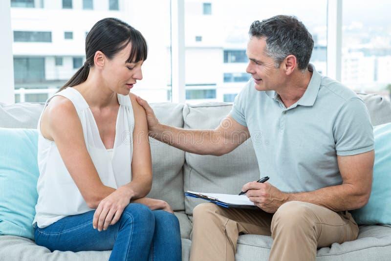 Terapeuta que consola uma mulher foto de stock
