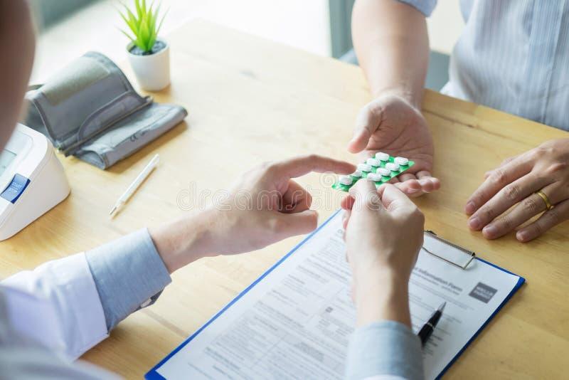 Terapeuta que consulta al paciente masculino paciente sobre píldoras que escribe su medicamento de venta con receta médico en la  imagen de archivo libre de regalías
