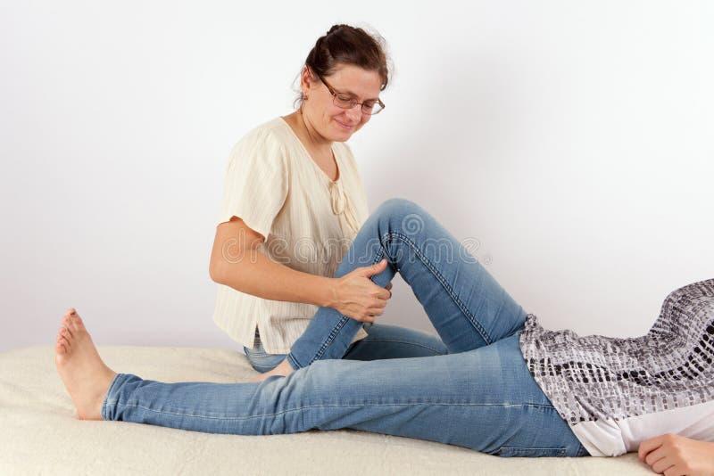 Terapeuta que dá o tratamento de Bowen para uma jovem mulher imagens de stock