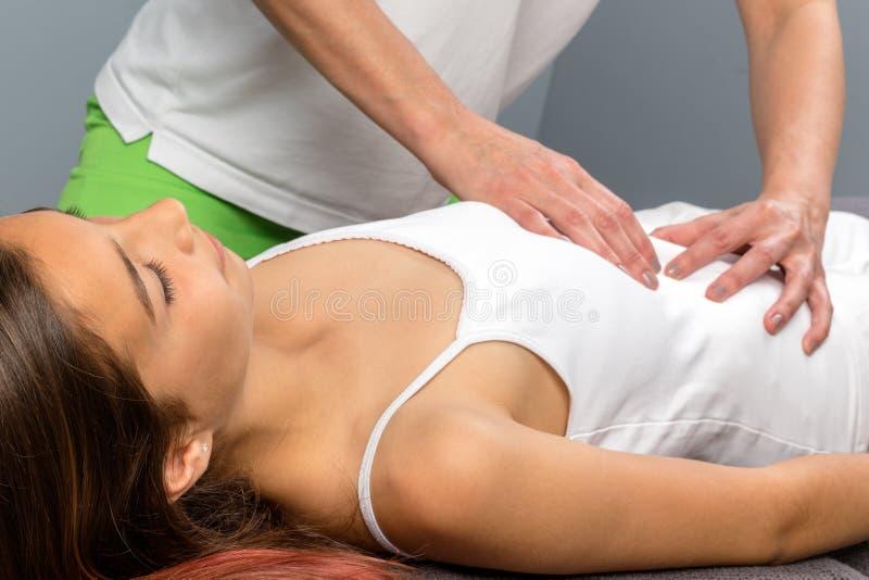 Terapeuta que faz a massagem da barriga na criança fotografia de stock