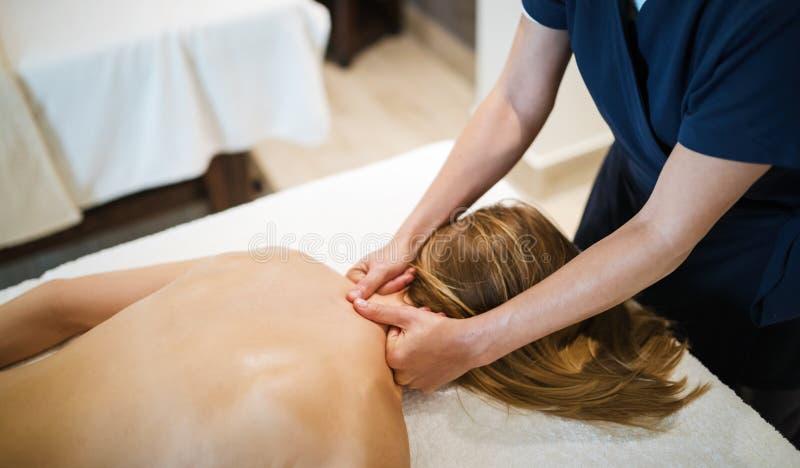 Terapeuta que faz massagens o paciente bonito em termas do bem-estar fotografia de stock