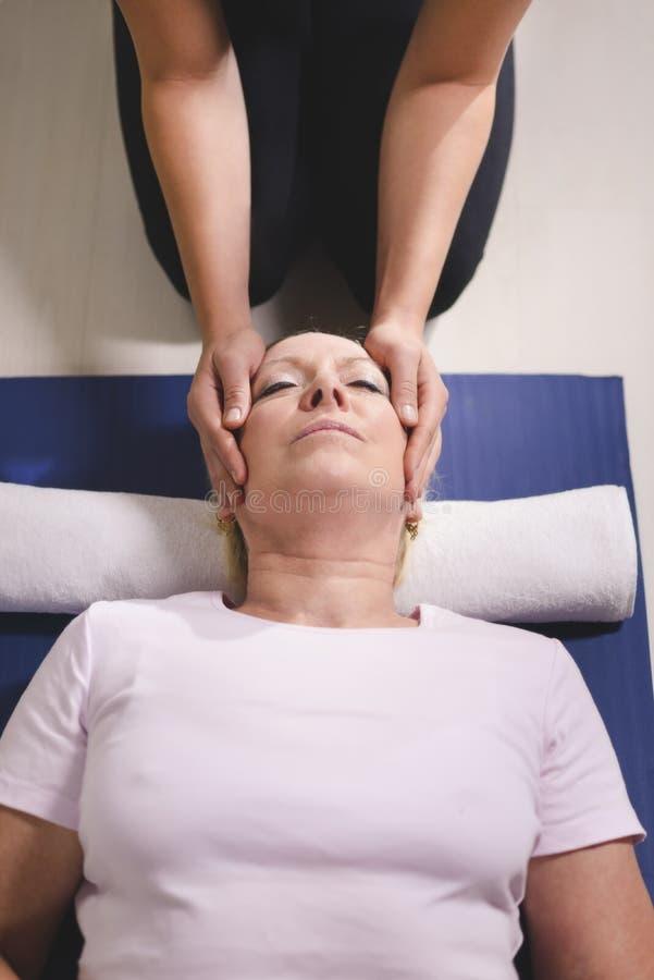 Terapeuta que faz a terapia do reiki à mulher sênior imagem de stock