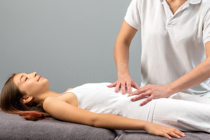 Terapeuta que hace masaje del abdomen en niña fotografía de archivo libre de regalías