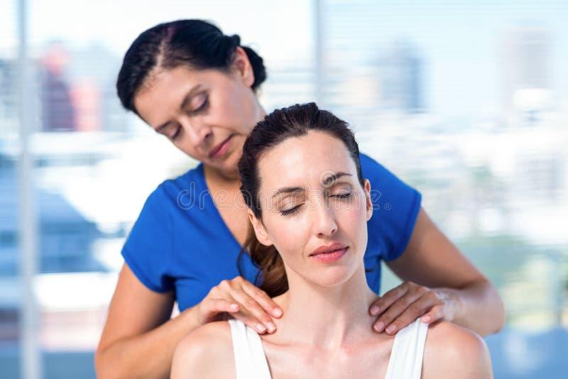 Terapeuta que hace masaje trasero a su paciente imagenes de archivo