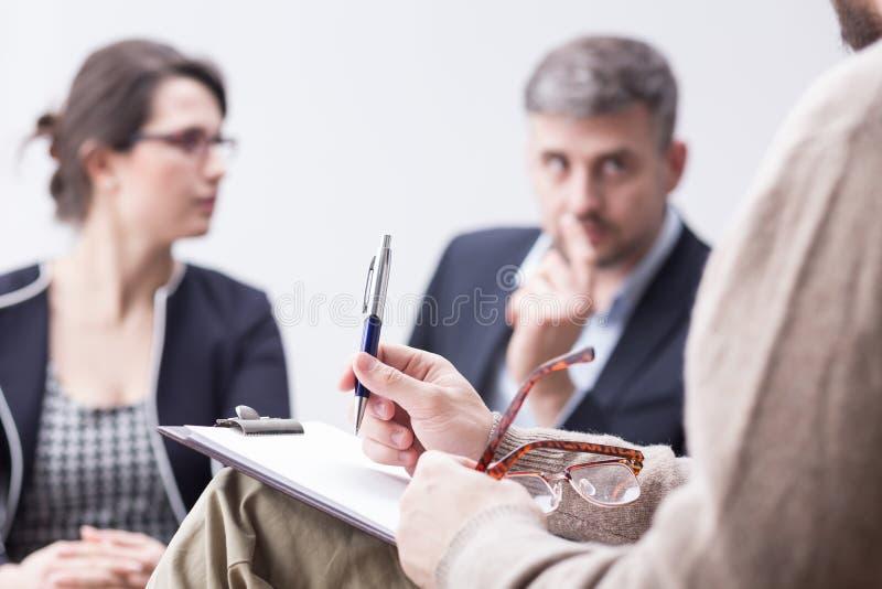 Terapeuta que toma notas durante a sessão de terapia da união foto de stock