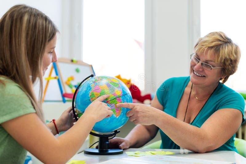 Terapeuta que trabalha com um adolescente com dificuldades de aprendizagem Sessão privada do tutoria da geografia Professor com e imagens de stock