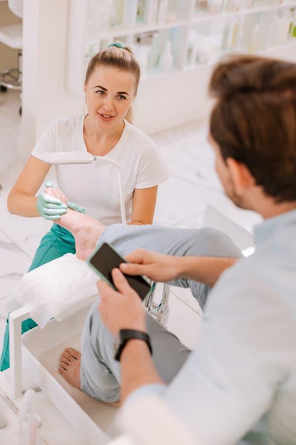 terapeuta Rubio-cabelludo del masaje que habla con su cliente constante imagen de archivo libre de regalías
