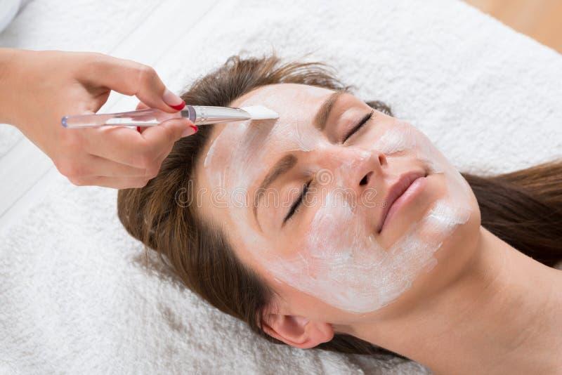 Terapeuta stosuje twarzy maskę kobieta obrazy stock