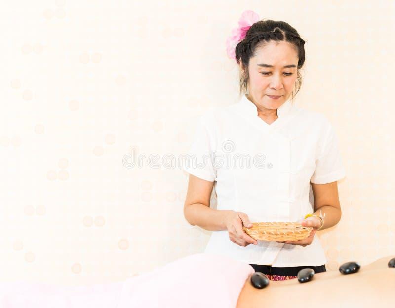 Terapeuta tailandés del balneario que da el tratamiento de piedra caliente a una mujer fotos de archivo