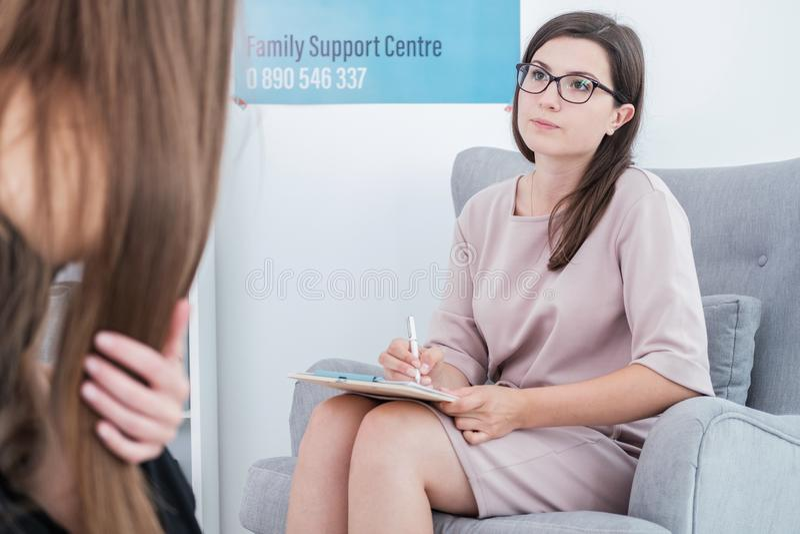 Terapeuta trzyma i opowiada jej pacjent w pióro i papiery, obrazy stock