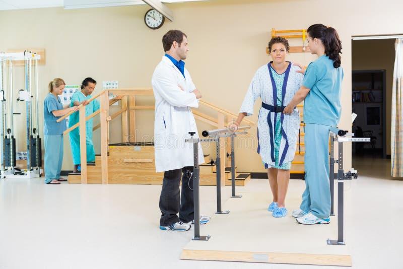 Terapeutas físicos que ayudan al paciente femenino adentro foto de archivo libre de regalías
