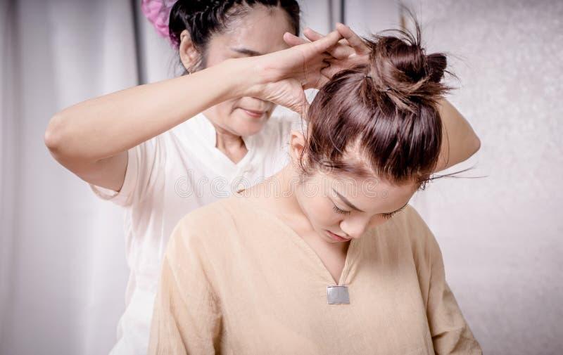 Terapeuten använder fingret för att massera kvinnor hånglar i thailändsk brunnsort arkivfoto