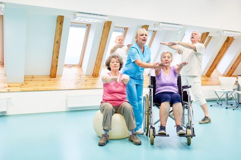 Terapeuten hjälper pensionärer i sjukgymnastik arkivbilder