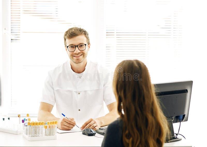 Terapeuten ser kameran, medan tala med en kvinnlig klient royaltyfri fotografi