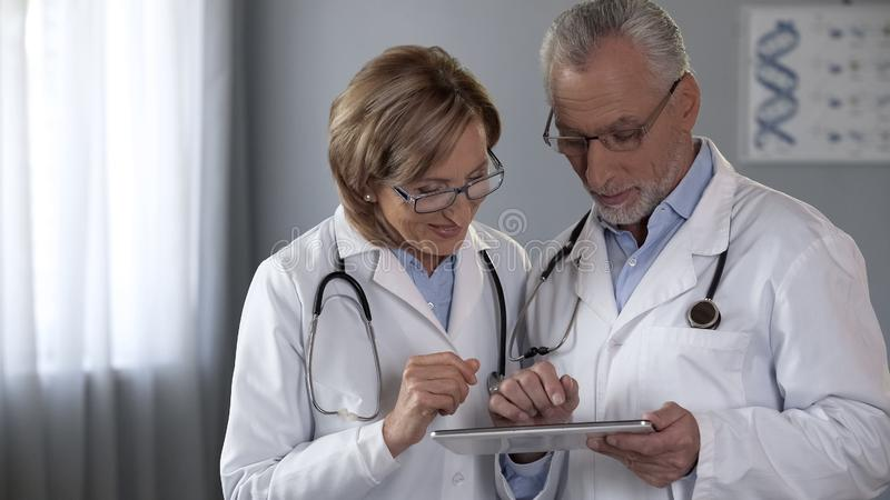 Terapeutlag som ser minnestavlan, genom att använda den moderna appen, teknologier i medicin royaltyfri fotografi