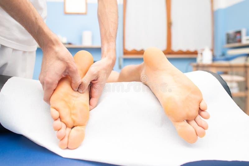 Terapeuts händer som masserar den manliga foten arkivbild