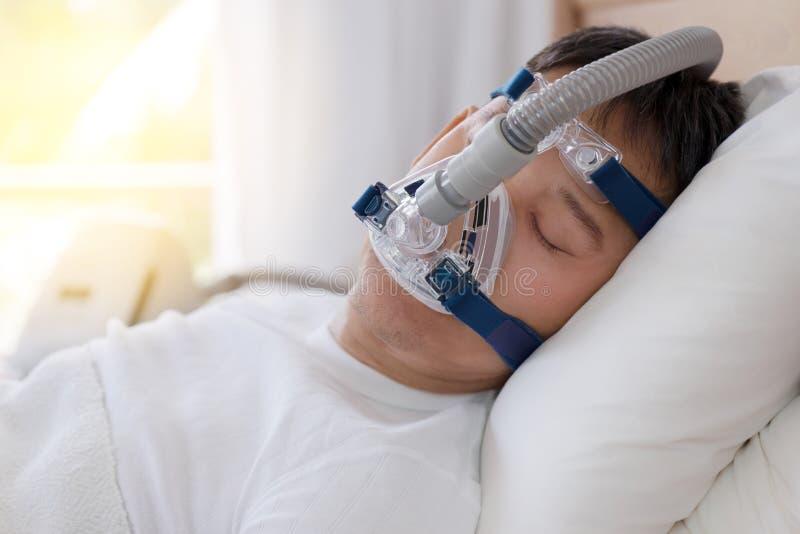 Terapia da apneia do sono, homem que dorme na cama que veste a máscara de CPAP foto de stock royalty free