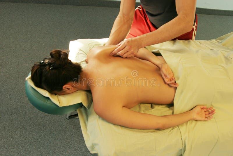 Terapia da massagem - terapeuta que dá a massagem traseira imagem de stock