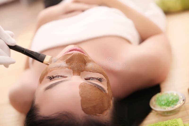 Terapia del balneario para la mujer joven que tiene máscara cosmética en el salón de belleza fotos de archivo libres de regalías
