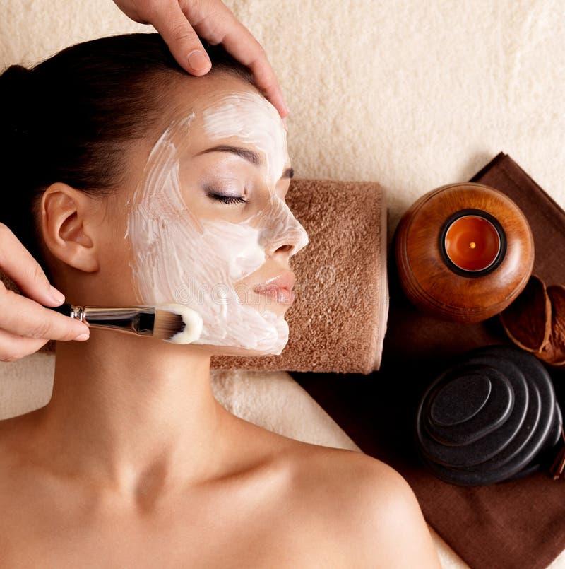 Terapia del balneario para la mujer que recibe la máscara facial foto de archivo