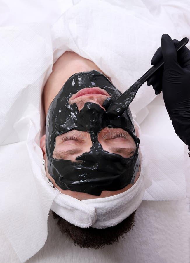 Terapia del balneario para los hombres que reciben la máscara negra facial fotos de archivo libres de regalías