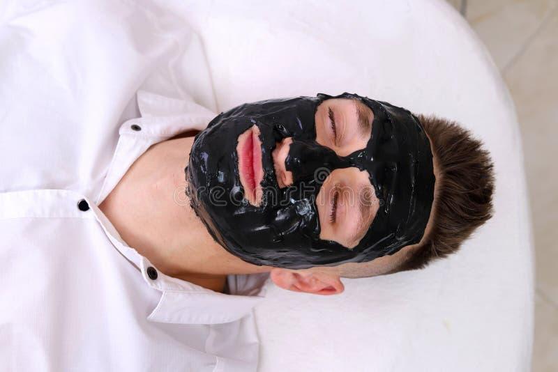 Terapia del balneario para los hombres que reciben la máscara negra facial foto de archivo