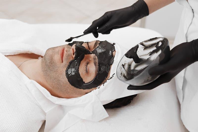 Terapia del balneario para los hombres que reciben la m?scara negra facial imágenes de archivo libres de regalías