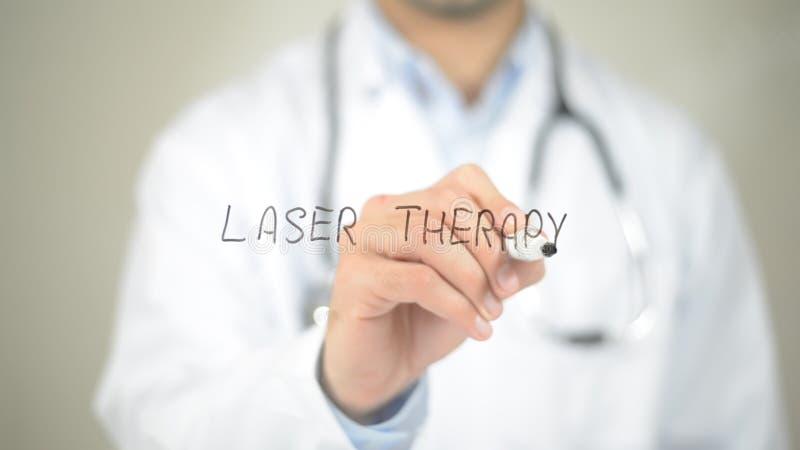 Terapia del laser, escritura del doctor en la pantalla transparente foto de archivo