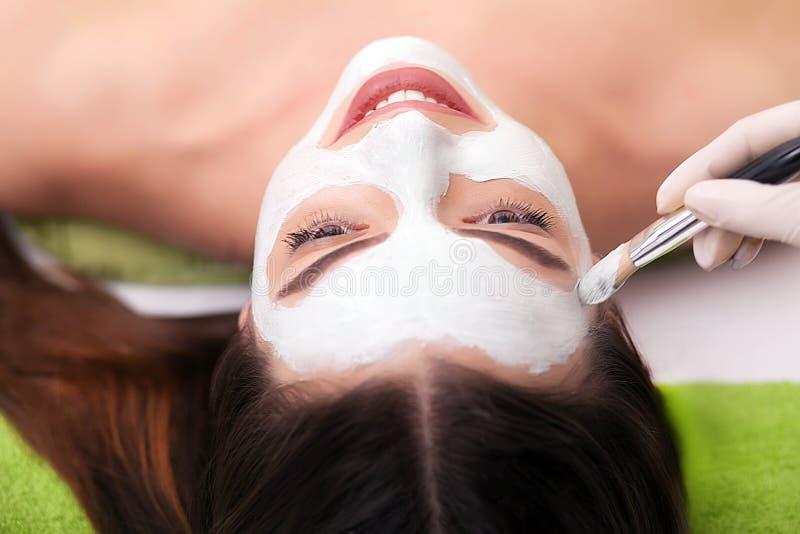 Terapia della stazione termale per la giovane donna che riceve maschera facciale al salone di bellezza - all'interno immagine stock libera da diritti