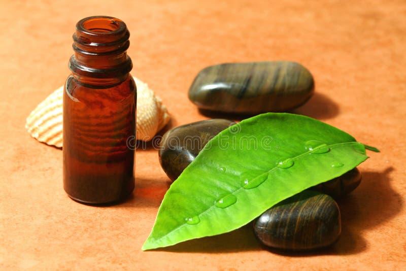 Terapia dos termas - petróleo com pedras da massagem fotografia de stock royalty free