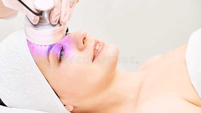 Terapia infrarossa leggera Procedura della testa di cosmetologia Fronte della donna di bellezza Dispositivo cosmetico del salone  fotografie stock libere da diritti