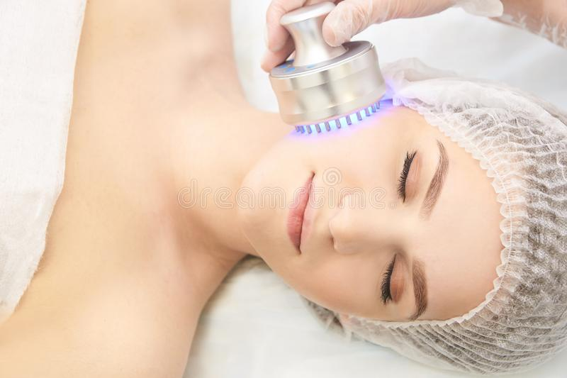 Terapia infravermelha clara Procedimento da cabe?a da cosmetologia Face da mulher da beleza Dispositivo cosm?tico do sal?o de bel fotos de stock royalty free