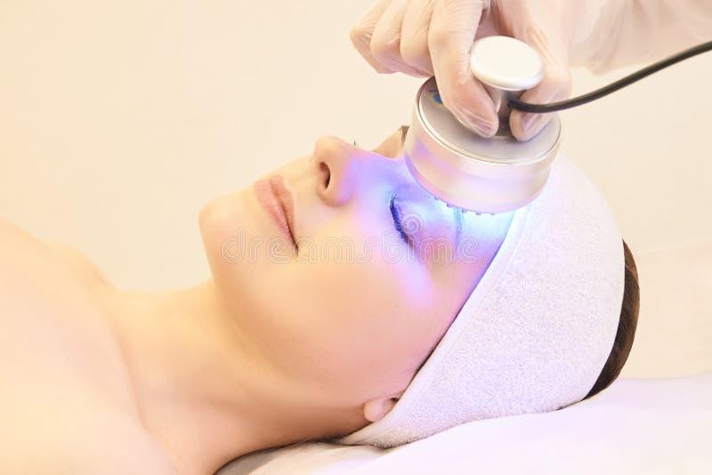 Terapia infravermelha clara Procedimento da cabe?a da cosmetologia Face da mulher da beleza Dispositivo cosm?tico do sal?o de bel imagens de stock royalty free