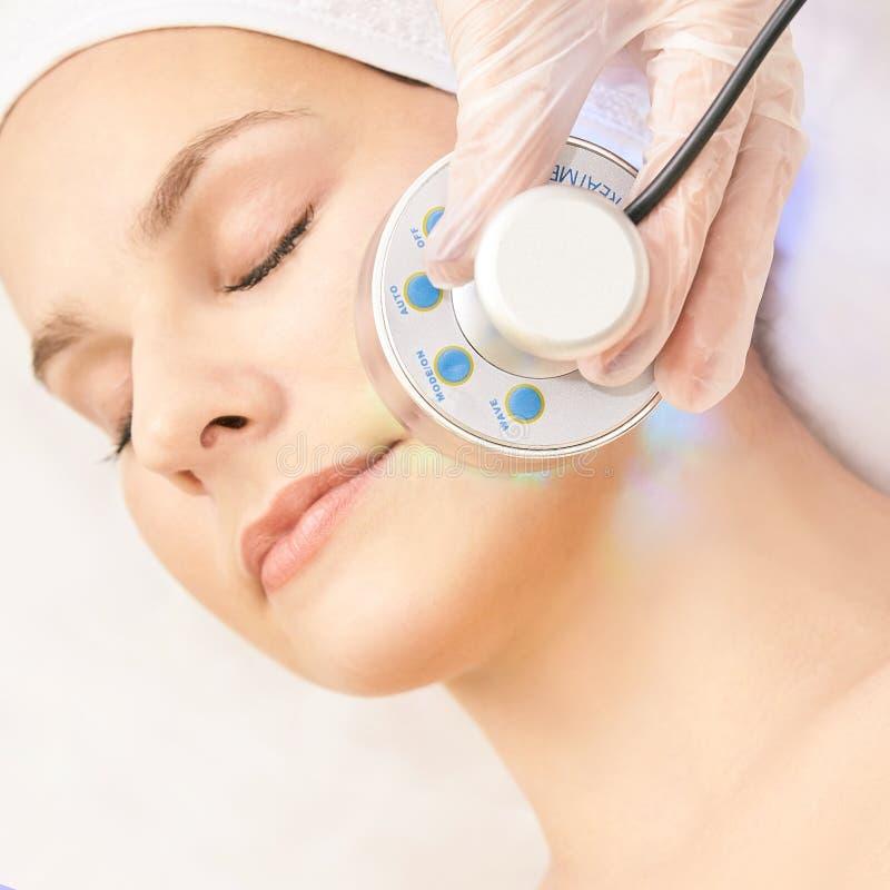 Terapia infravermelha clara Procedimento da cabe?a da cosmetologia Face da mulher da beleza Dispositivo cosm?tico do sal?o de bel foto de stock royalty free