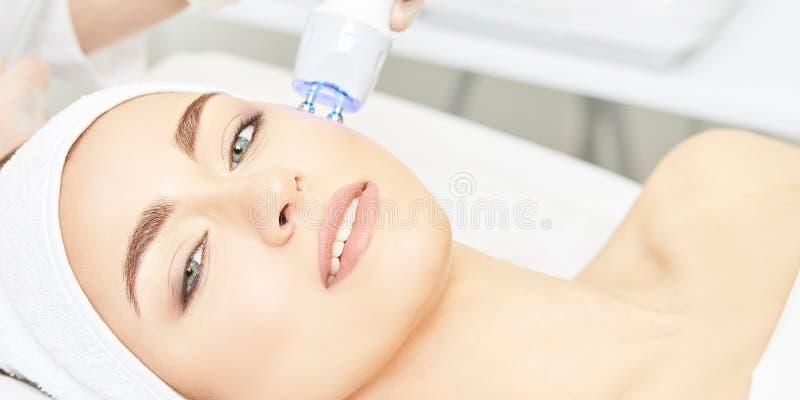 Terapia infravermelha clara Procedimento da cabe?a da cosmetologia Face da mulher da beleza Dispositivo cosm?tico do sal?o de bel imagem de stock