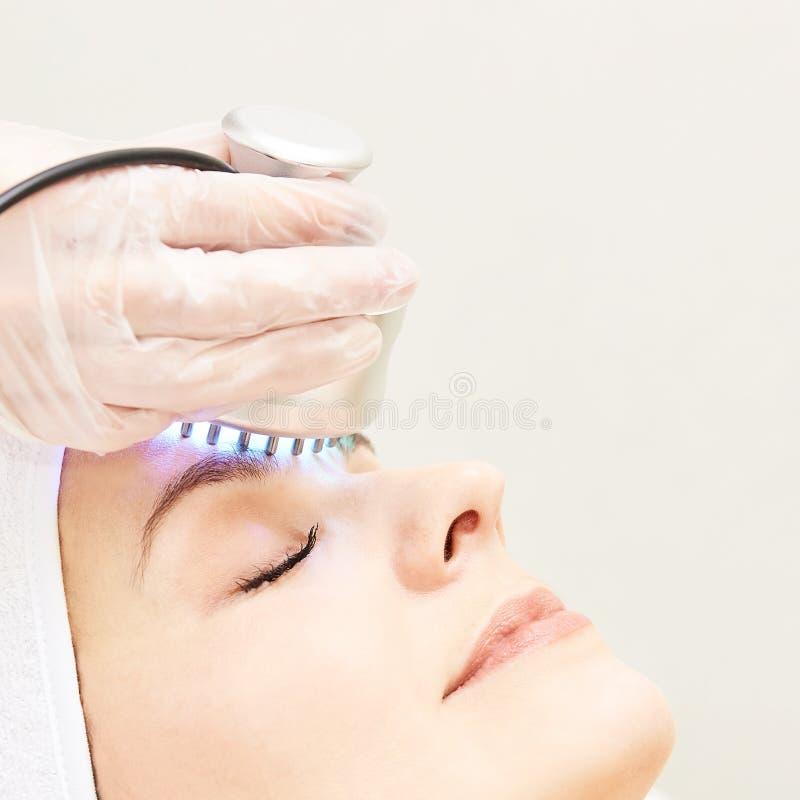 Terapia infravermelha clara Procedimento da cabe?a da cosmetologia Face da mulher da beleza Dispositivo cosm?tico do sal?o de bel fotografia de stock royalty free