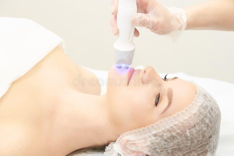 Terapia infravermelha clara Procedimento da cabe?a da cosmetologia Face da mulher da beleza Dispositivo cosm?tico do sal?o de bel foto de stock