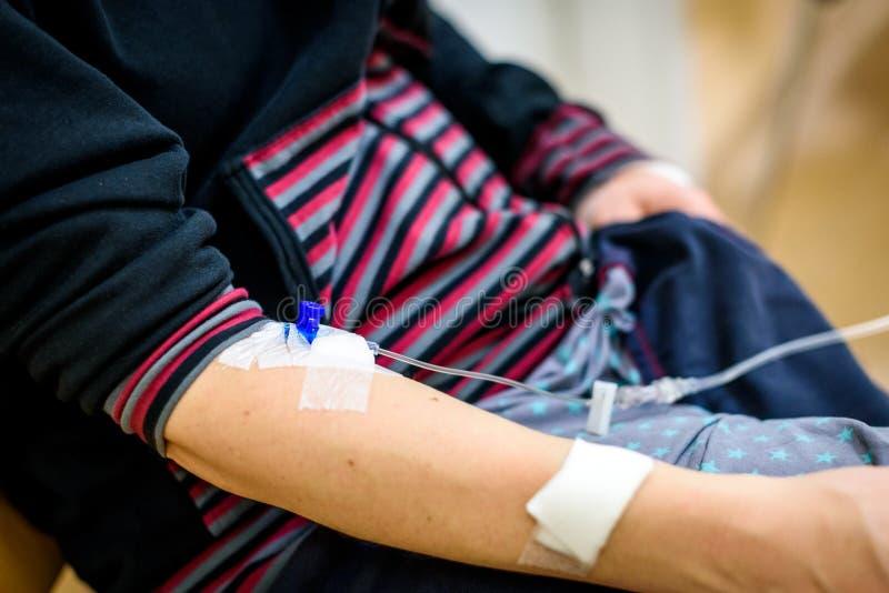 Terapia, infusione o dispositivo di venipunzione endovenosa in mano della donna in ospedale fotografie stock