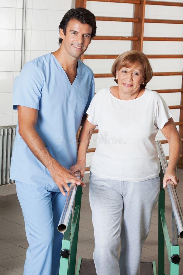Terapista Assisting Senior Woman da camminare con fotografia stock